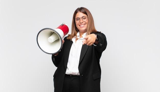 Mulher jovem com um megafone apontando para a câmera com um sorriso satisfeito, confiante e amigável, escolhendo você