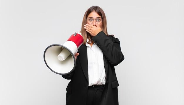 Mulher jovem com um megafone cobrindo a boca com as mãos e uma expressão chocada e surpresa, mantendo um segredo ou dizendo oops