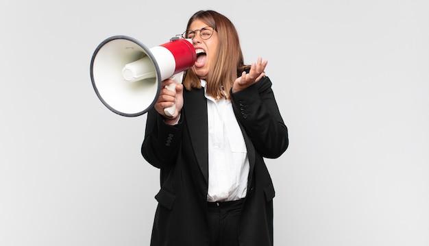 Mulher jovem com um megafone parecendo desesperada e frustrada, estressada, infeliz e irritada, gritando e gritando