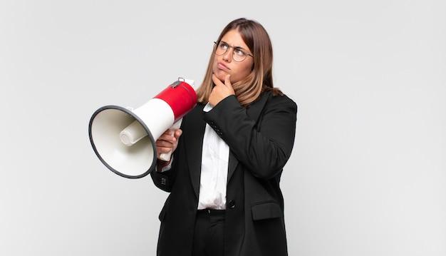 Mulher jovem com um megafone pensando, sentindo-se duvidosa e confusa, com diferentes opções, se perguntando qual decisão tomar