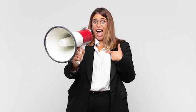Mulher jovem com um megafone se sentindo feliz, surpresa e orgulhosa