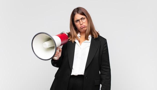 Mulher jovem com um megafone se sentindo triste e chorona com uma aparência infeliz, chorando com uma atitude negativa e frustrada