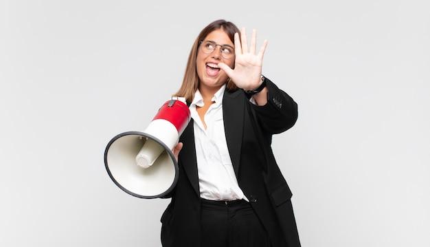 Mulher jovem com um megafone sorrindo e parecendo amigável, mostrando o número cinco ou quinto com a mão para a frente, em contagem regressiva