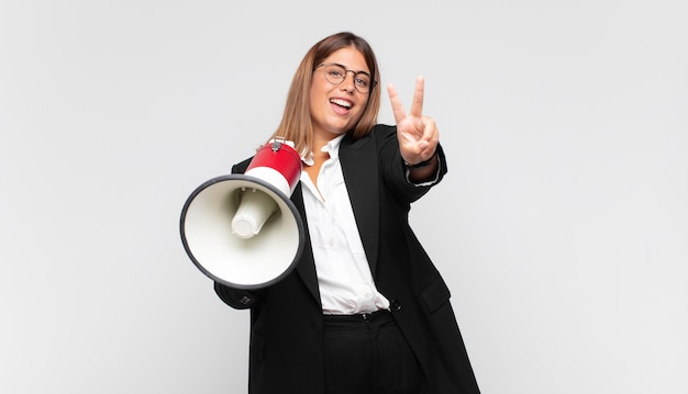 Mulher jovem com um megafone sorrindo e parecendo amigável, mostrando o número dois ou o segundo com a mão para a frente, em contagem regressiva