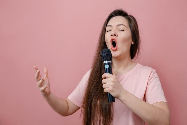 Mulher jovem com um microfone na mão em um fundo rosa canta como uma cantora de ópera