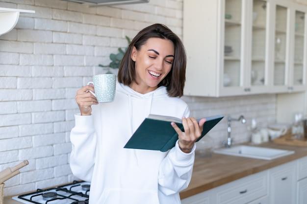 Mulher jovem com um moletom branco quente em casa na cozinha lendo um livro pela manhã