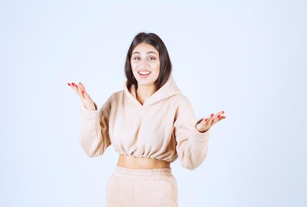 Mulher jovem com um moletom rosa apresentando algo na mão aberta