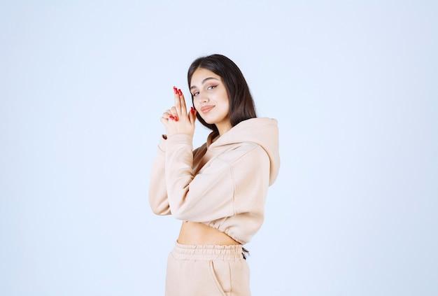 Mulher jovem com um moletom rosa mostrando o sinal da arma