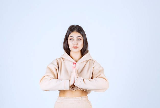 Mulher jovem com um moletom rosa unindo as mãos e orando
