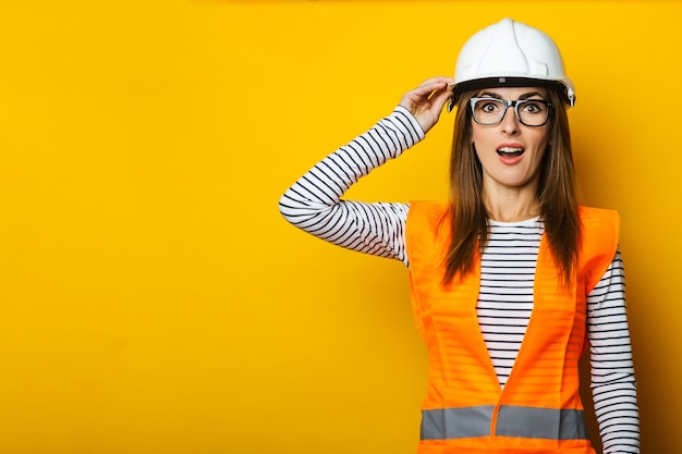 Mulher jovem com um rosto surpreso com um colete e capacete amarelo