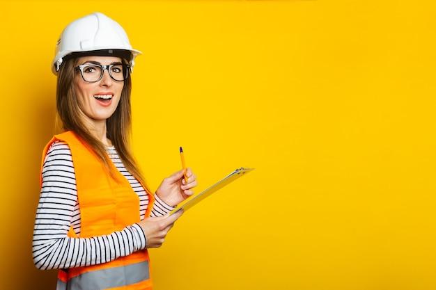 Mulher jovem com um rosto surpreso usando um colete e capacete segurando uma prancheta amarela