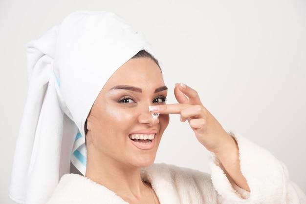 Mulher jovem com um roupão de banho branco aplicando um creme no nariz