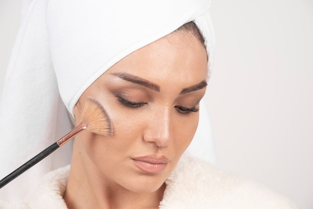 Mulher jovem com um roupão de banho segurando um pincel de maquiagem