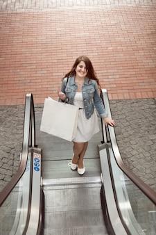 Mulher jovem com um saco de papel subindo na escada rolante de um shopping
