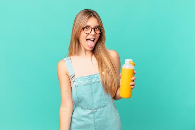 Mulher jovem com um smoothy com atitude alegre e rebelde, brincando e mostrando a língua