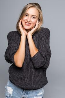 Mulher jovem com um sorriso amigável e pensativo, olhando de lado para a câmera com a cabeça inclinada para o lado e copia o espaço
