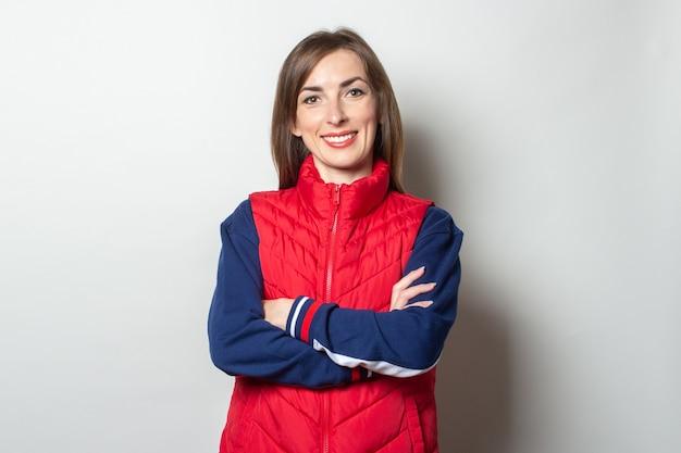 Mulher jovem com um sorriso cruzou os braços sobre o peito em um colete vermelho contra uma parede de luz