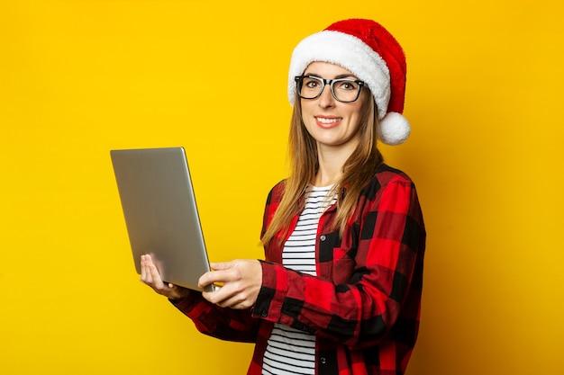 Mulher jovem com um sorriso em um chapéu de papai noel e uma camisa vermelha em uma gaiola segurando um laptop
