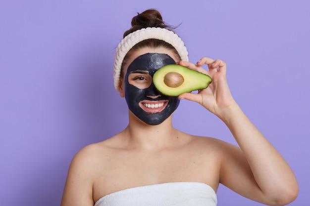 Mulher jovem com um sorriso segurando abacate e cobrindo os olhos com ele