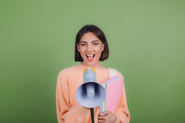 Mulher jovem com um suéter casual cor de pêssego e uma mochila isolada na parede verde oliva