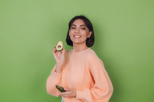 Mulher jovem com um suéter casual cor de pêssego, isolado em uma parede verde oliva, segurando um abacate, um conceito de saúde e cuidados com a pele, copie o espaço