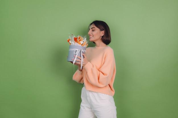Mulher jovem com um suéter casual cor de pêssego isolado em uma parede verde oliva