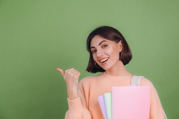 Mulher jovem com um suéter casual cor de pêssego isolado na parede verde oliva