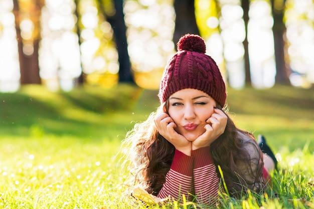 Mulher jovem com um suéter marrom e um gorro de malha curtindo o outono no parque
