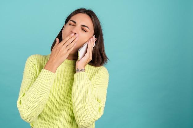 Mulher jovem com um suéter verde claro com telefone celular conversando e ouvindo mensagem de áudio