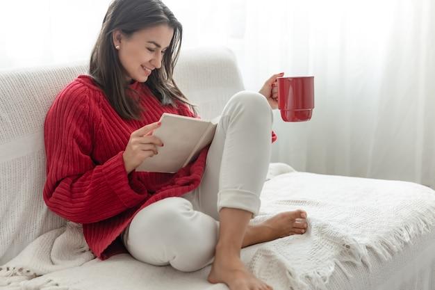 Mulher jovem com um suéter vermelho com uma xícara vermelha lê um livro.