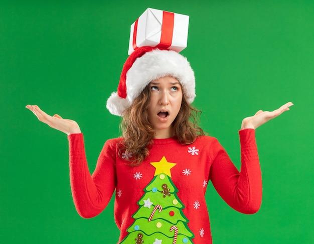 Mulher jovem com um suéter vermelho de natal e um chapéu de papai noel com um presente na cabeça, parecendo confusa, abrindo os braços para os lados em pé sobre um fundo verde