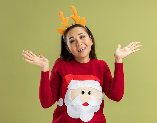 Mulher jovem com um suéter vermelho de natal, vestindo uma jaqueta engraçada com chifres de veado, sorrindo com os braços levantados.