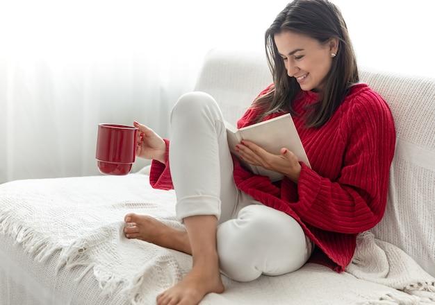 Mulher jovem com um suéter vermelho e uma xícara vermelha lê um livro.