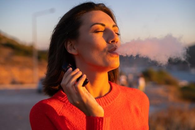 Mulher jovem com um suéter vermelho em um pôr do sol magnífico na montanha aprecia um cigarro eletrônico