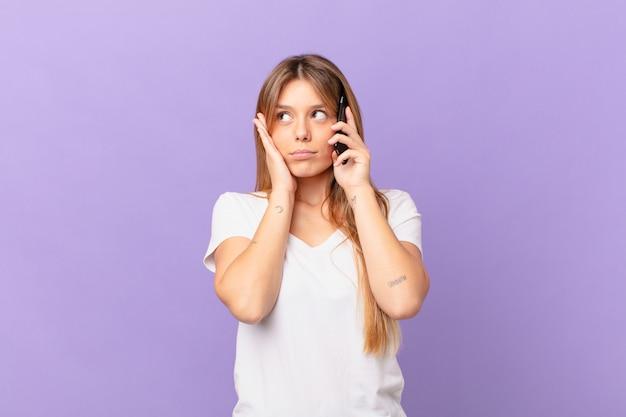 Mulher jovem com um telefone celular se sentindo entediada, frustrada e com sono após um período cansativo