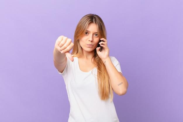 Mulher jovem com um telefone celular se sentindo zangada e mostrando os polegares para baixo