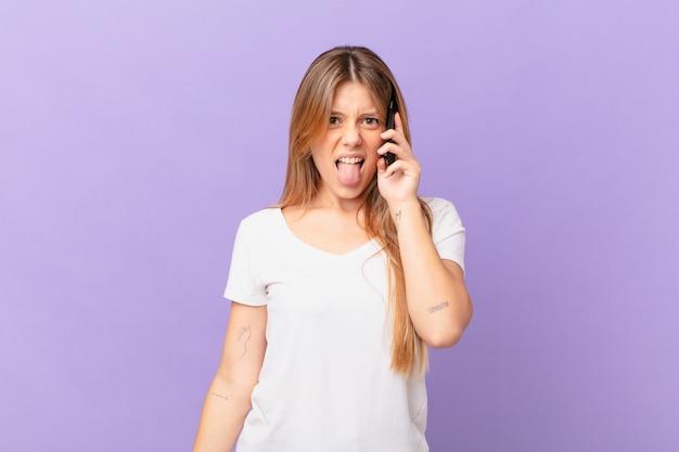 Mulher jovem com um telefone celular sentindo-se enojada e irritada e com a língua de fora