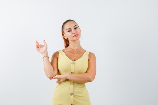 Mulher jovem com um vestido amarelo a apontar para trás e parecendo confiante