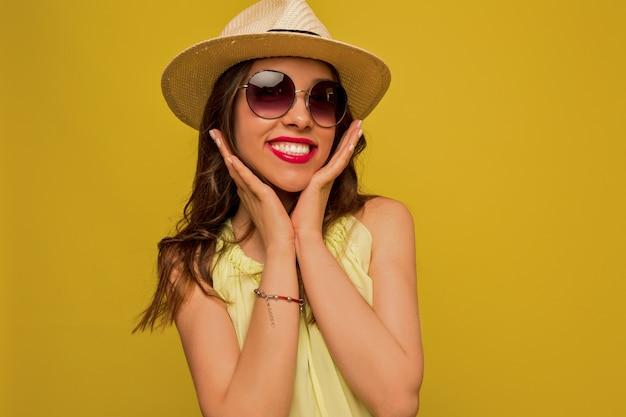 Mulher jovem com um vestido amarelo com chapéu e óculos de sol
