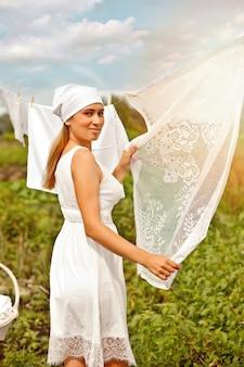Mulher jovem com um vestido branco pendurando roupa ao ar livre