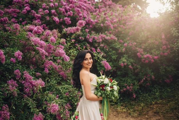 Mulher jovem com um vestido de peônia em um jardim lilás florido ao pôr do sol