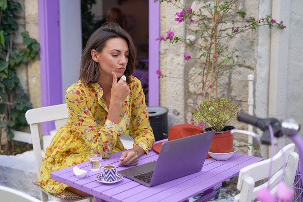 Mulher jovem com um vestido em um café de rua iluminada com um laptop trabalha remotamente em sua própria programação, em qualquer lugar do mundo on-line