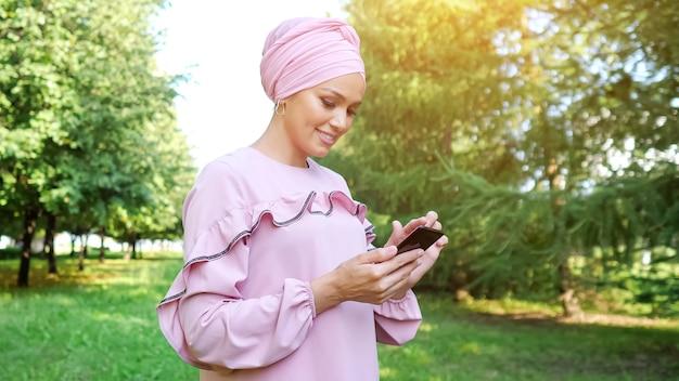 Mulher jovem com um vestido rosa de grife e tipos de hijab em um smartphone preto em pé contra árvores verdes em um parque local em um dia ensolarado de verão