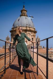 Mulher jovem com um vestido verde no telhado de um templo católico