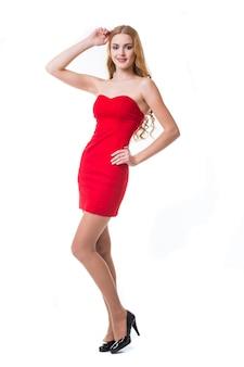 Mulher jovem com um vestido vermelho dançando no fundo branco