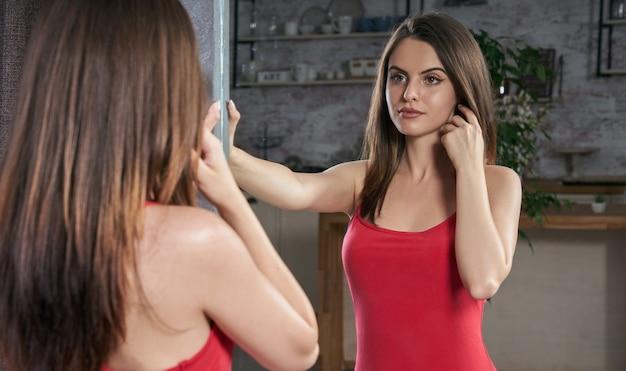 Mulher jovem com um vestido vermelho e se olhando no espelho