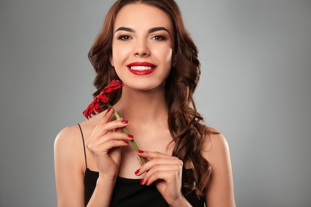 Mulher jovem com uma bela manicure e flores em cinza