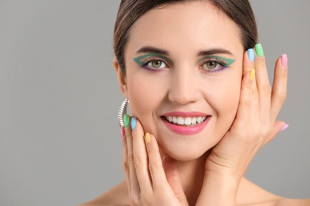 Mulher jovem com uma bela manicure em fundo cinza