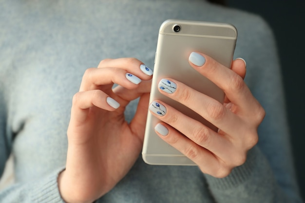 Mulher jovem com uma bela manicure segurando o telefone, close-up