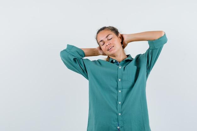 Mulher jovem com uma blusa verde de mãos dadas atrás dos braços enquanto fecha os olhos e parece exausta